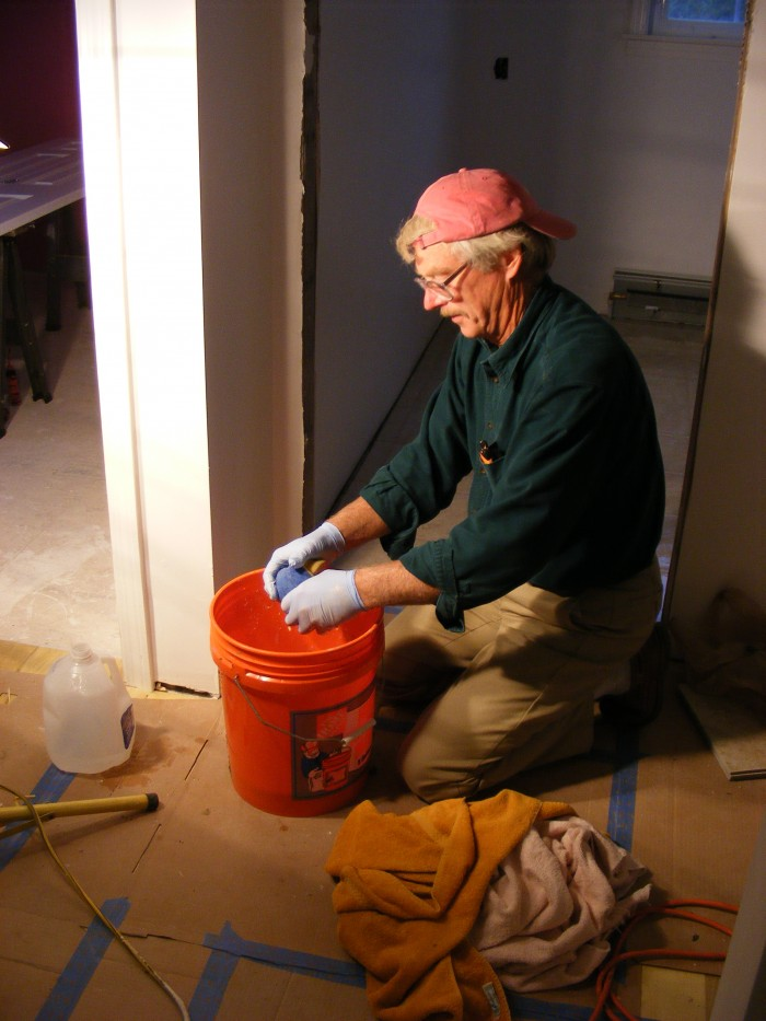 Volunteer, Bill, grouts the tile he installed.